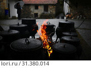 Купить «During Carnival Truesday, in the streets of the village, black iron pots over the fire cook a meathy soup for everyone.», фото № 31380014, снято 28 февраля 2017 г. (c) age Fotostock / Фотобанк Лори