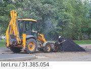 Рабочий с лопатой работает у желтого трактора рядом с кучей горячего дымящегося асфальта. Ремонт дорожного покрытия на улице города. Стоковое фото, фотограф Наталья Николаева / Фотобанк Лори