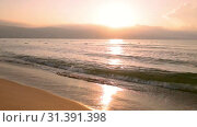 Купить «Sunrise over the sea, the waves of the surf rolled on the sandy beach», видеоролик № 31391398, снято 26 июня 2019 г. (c) Юлия Бабкина / Фотобанк Лори