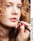 Купить «Makeup artist visagiste using brush for application lipstick on lips of young caucasian model with wavy ginger hair», фото № 31391950, снято 9 июня 2019 г. (c) Serg Zastavkin / Фотобанк Лори
