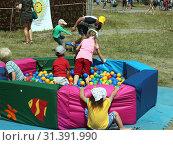 Купить «На детской площадке 46-го Грушинского фестиваля дети играют в сухом бассейне, наполненном разноцветными шариками», фото № 31391990, снято 6 июля 2019 г. (c) Светлана Кириллова / Фотобанк Лори
