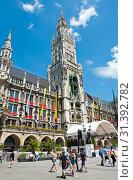 Туристы на площади Мариенплац рядом с Новой ратушей (Neues Rathaus) в летний солнечный день. Мюнхен. Бавария. Германия (2019 год). Редакционное фото, фотограф E. O. / Фотобанк Лори