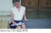 Купить «Higher education happy girl freshwoman student sitting on university steps», видеоролик № 31422474, снято 9 июля 2019 г. (c) Gennadiy Poznyakov / Фотобанк Лори