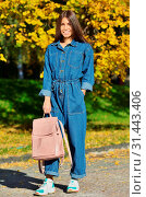 Купить «Girl denim clothes holding a pink backpack on a background of yellow autumn in the campus», фото № 31443406, снято 13 октября 2018 г. (c) easy Fotostock / Фотобанк Лори