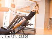 young beautiful girl in short sport shorts and a black sleeveless jersey engaged in fitness in the gym. Стоковое фото, фотограф katalinks / Фотобанк Лори