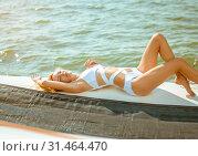 Купить «Young beautiful slim sexy girl in bikini and pareo is resting on cruise on a private sailing yacht», фото № 31464470, снято 25 июля 2017 г. (c) katalinks / Фотобанк Лори