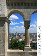 Купить «Beautiful view of the city and the Hungarian parliament building through the wall and arches of the Fisherman's Bastion on a sunny summer day in Budapest, Hungary», фото № 31467578, снято 3 июня 2019 г. (c) Яна Королёва / Фотобанк Лори