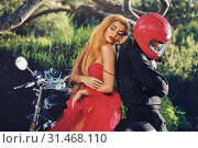 Купить «Lady wearing red dress sitting on motorcycle with man, girl leaned on guy hides his face behind helmet pose on nature, sunny summer day two people outdoors near bike, hobby lifestyle fashion concept», фото № 31468110, снято 29 мая 2019 г. (c) Alexander Tihonovs / Фотобанк Лори