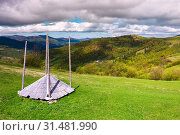 Купить «Hay shed on a slope of mountainous rural area. beautiful view of rural fields on hills and a village in valey. lovely countryside landscape in springtime on a clloudy day», фото № 31481990, снято 9 мая 2017 г. (c) easy Fotostock / Фотобанк Лори