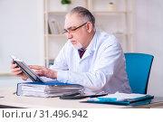 Купить «Old male doctor working in the clinic», фото № 31496942, снято 26 марта 2019 г. (c) Elnur / Фотобанк Лори