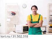 Купить «Young repairman repairing microwave in service centre», фото № 31502318, снято 27 февраля 2019 г. (c) Elnur / Фотобанк Лори