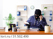Купить «Male thief in balaclava in the office», фото № 31502490, снято 8 февраля 2019 г. (c) Elnur / Фотобанк Лори