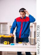 Купить «Young contractor repairing furniture at home», фото № 31502730, снято 7 декабря 2018 г. (c) Elnur / Фотобанк Лори