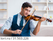 Купить «Young musician man practicing playing violin at home», фото № 31503226, снято 15 августа 2017 г. (c) Elnur / Фотобанк Лори