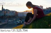 Купить «Young ballerina fastens the tug on her pointe sitting on a green hill in the middle of the city.», видеоролик № 31525794, снято 27 мая 2020 г. (c) Константин Шишкин / Фотобанк Лори