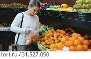 Купить «Young woman searching for fresh fruits while shopping in greengrocery», видеоролик № 31527050, снято 12 февраля 2019 г. (c) Яков Филимонов / Фотобанк Лори
