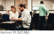 Купить «Focused bearded freelancer concentrated on work with laptop in coworking space with international team», видеоролик № 31527082, снято 12 апреля 2019 г. (c) Яков Филимонов / Фотобанк Лори