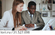 Купить «Young woman and man colleagues working at laptop and discussing in office», видеоролик № 31527098, снято 26 апреля 2019 г. (c) Яков Филимонов / Фотобанк Лори