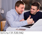 Купить «Adult male with his son are resting together and playing on laptop», фото № 31530942, снято 5 февраля 2018 г. (c) Яков Филимонов / Фотобанк Лори