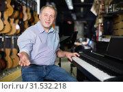 Купить «Smiling musician is playing on modern keyboard», фото № 31532218, снято 18 сентября 2017 г. (c) Яков Филимонов / Фотобанк Лори