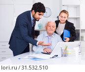 Купить «Office workers are demonstrating reports on laptop to mature boss», фото № 31532510, снято 27 июня 2017 г. (c) Яков Филимонов / Фотобанк Лори