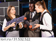 Купить «Smiling associates – afro man and two European women posing at laser tag room», фото № 31532522, снято 4 апреля 2019 г. (c) Яков Филимонов / Фотобанк Лори