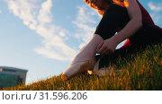 Купить «Young attractive ballerina takes on pointe shoes and wears a sitting on the green hill.», видеоролик № 31596206, снято 27 мая 2020 г. (c) Константин Шишкин / Фотобанк Лори