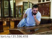 Купить «Attentive adult man exploring artworks in glass case in museum», фото № 31596418, снято 7 апреля 2019 г. (c) Яков Филимонов / Фотобанк Лори