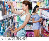 Купить «Woman customer looking for mouthwash at store», фото № 31596434, снято 21 июня 2018 г. (c) Яков Филимонов / Фотобанк Лори