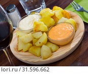 Купить «Traditional Spanish fried potatoes Patatas bravas served with cheese sauce and spicy sauce», фото № 31596662, снято 6 июня 2020 г. (c) Яков Филимонов / Фотобанк Лори