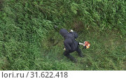Купить «Мужчина косит зеленую траву ручной бензиновой газонокосилкой. Вид сверху», видеоролик № 31622418, снято 17 июля 2019 г. (c) А. А. Пирагис / Фотобанк Лори