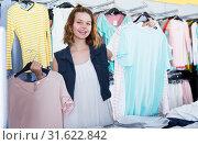 Купить «Young woman shopper choosing new garments», фото № 31622842, снято 19 июня 2017 г. (c) Яков Филимонов / Фотобанк Лори