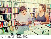 Купить «portrait of teenage boy and girl customers looking at open book», фото № 31622902, снято 16 сентября 2016 г. (c) Яков Филимонов / Фотобанк Лори