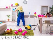 Купить «Young male contractor doing housework after party», фото № 31624062, снято 14 марта 2019 г. (c) Elnur / Фотобанк Лори