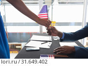 Купить «Business people holding an American flag at conference registration table», фото № 31649402, снято 16 марта 2019 г. (c) Wavebreak Media / Фотобанк Лори