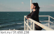 Beautiful woman with long black hair is standing on the pier and enjoing the awesome view on sea after morning workout outdoors slow motion. Стоковое видео, видеограф Denis Mishchenko / Фотобанк Лори