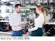 Купить «Assistant helping customer to choose saucepan», фото № 31650406, снято 8 февраля 2017 г. (c) Яков Филимонов / Фотобанк Лори
