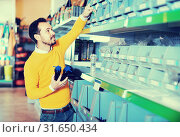 Купить «Man choosing various tools in garden equipment shop», фото № 31650434, снято 2 марта 2017 г. (c) Яков Филимонов / Фотобанк Лори