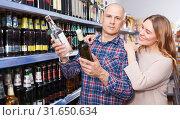 Family couple choosing alcohol products in hypermarket. Стоковое фото, фотограф Яков Филимонов / Фотобанк Лори
