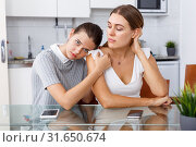 Sad women sitting at table after conflict and holding head at home. Стоковое фото, фотограф Яков Филимонов / Фотобанк Лори