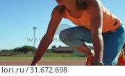 Купить «Front view of Caucasian female athlete taking starting position on a running track at sports venue 4», видеоролик № 31672698, снято 17 апреля 2018 г. (c) Wavebreak Media / Фотобанк Лори