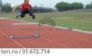 Купить «Side view of Caucasian female athlete jumping over hurdle on race track 4k», видеоролик № 31672714, снято 17 апреля 2018 г. (c) Wavebreak Media / Фотобанк Лори