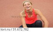 Купить «Front view of Caucasian female athlete tying shoelace on running track 4k», видеоролик № 31672782, снято 17 апреля 2018 г. (c) Wavebreak Media / Фотобанк Лори
