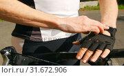 Senior cyclist wearing fingerless gloves at countryside 4k. Стоковое видео, агентство Wavebreak Media / Фотобанк Лори