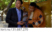 Купить «Commuters using mobile phone at bus stop 4k», видеоролик № 31687270, снято 10 июня 2018 г. (c) Wavebreak Media / Фотобанк Лори