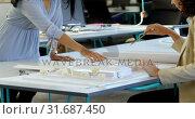 Купить «Executives discussing over architectural model in the office 4k», видеоролик № 31687450, снято 1 сентября 2018 г. (c) Wavebreak Media / Фотобанк Лори