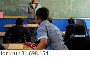 Купить «Male teacher teaching students in the class 4k», видеоролик № 31698154, снято 8 августа 2018 г. (c) Wavebreak Media / Фотобанк Лори