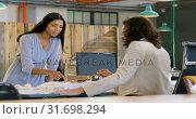Купить «Executives discussing over architectural model in the office 4k», видеоролик № 31698294, снято 1 сентября 2018 г. (c) Wavebreak Media / Фотобанк Лори