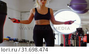 Купить «Female boxer exercising with skipping rope in fitness studio 4k», видеоролик № 31698474, снято 6 сентября 2018 г. (c) Wavebreak Media / Фотобанк Лори