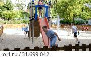 Купить «Cheerful boy and girl play games and running around sliding toy in park», видеоролик № 31699042, снято 23 июля 2018 г. (c) Яков Филимонов / Фотобанк Лори
